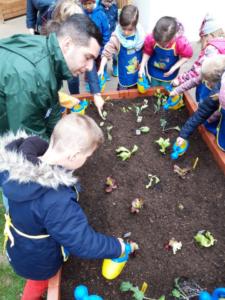 Kindergartenkinder gießen Pflanzen im neuen Hochbeet